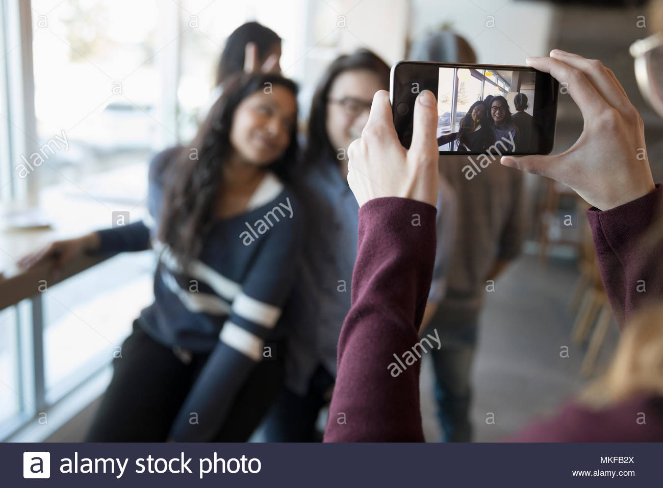 Young woman with camera phone photographing friends - Stock Image