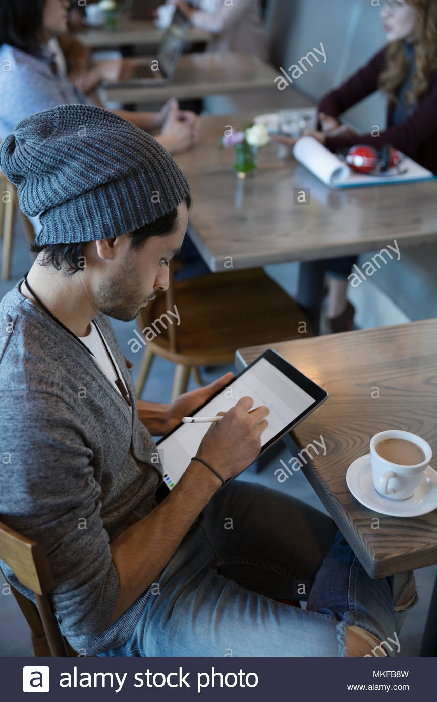 Creative young man drawing, using stylus on digital tablet at cafe - Stock Image