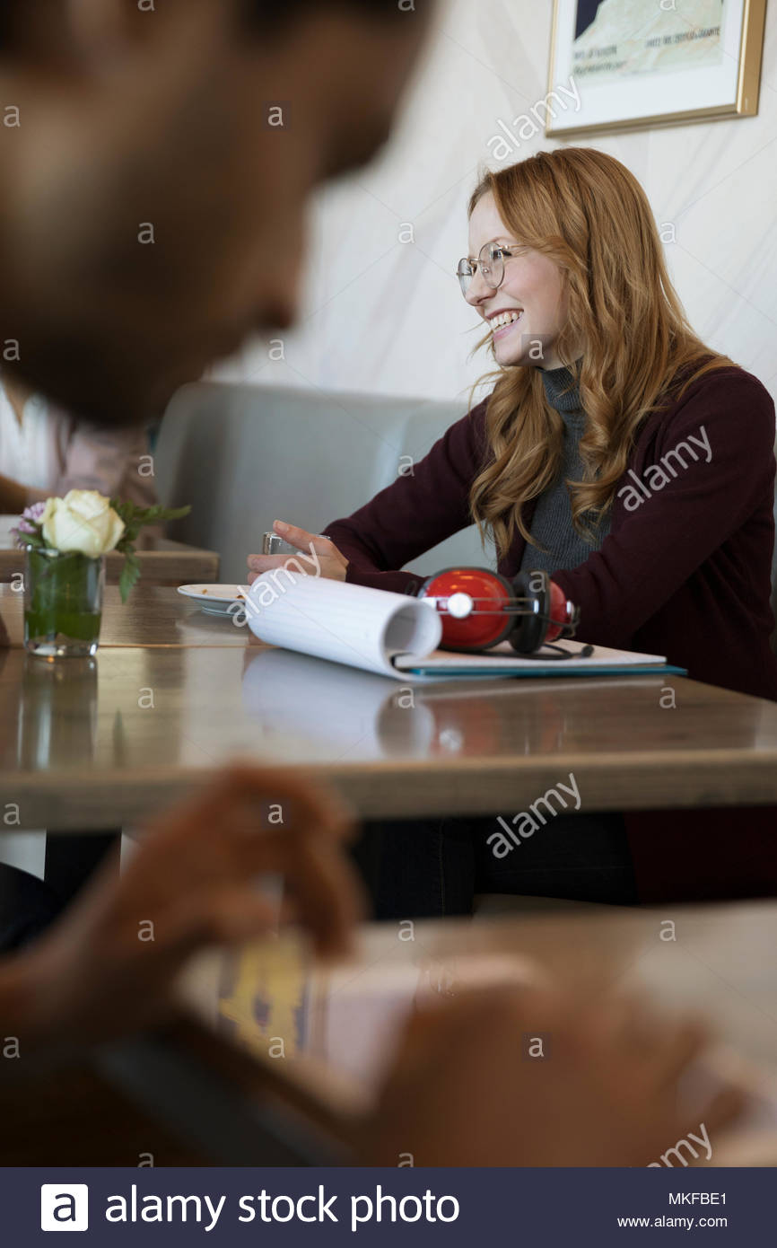 Smiling young businesswoman working in cafe - Stock Image