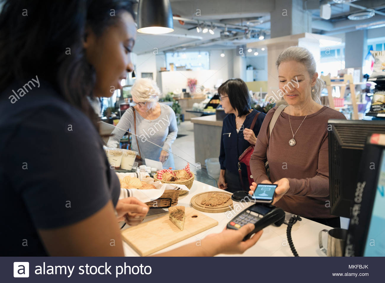 Senior woman with smart phone using contactless payment at bakery checkout Stock Photo
