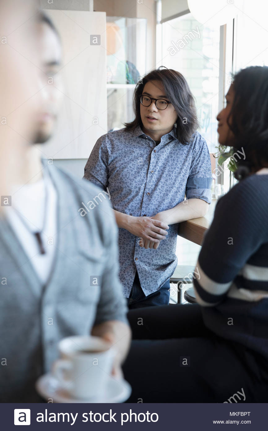 Young man talking with friends in cafe - Stock Image