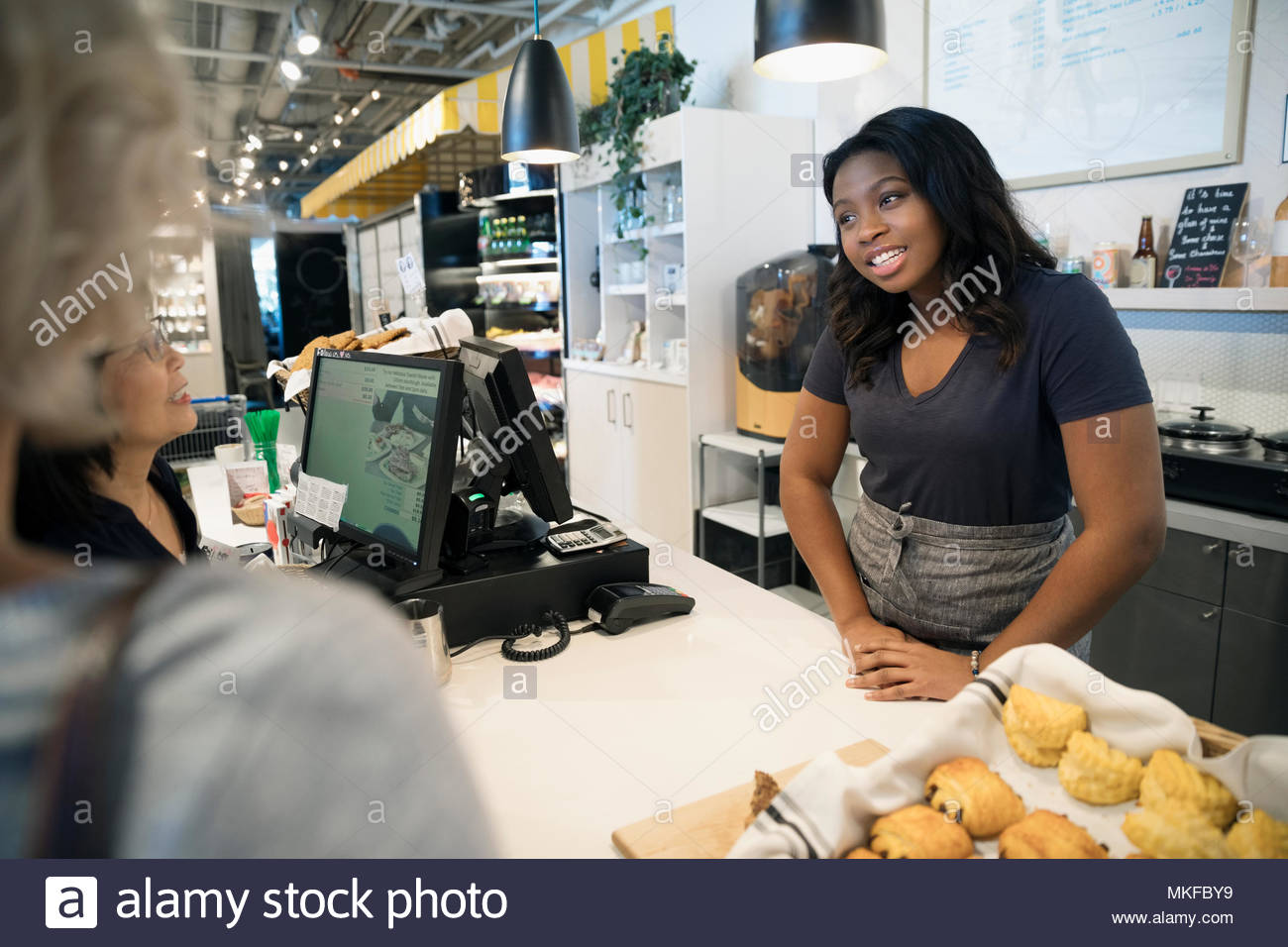 Smiling female small business owner working behind bakery counter - Stock Image