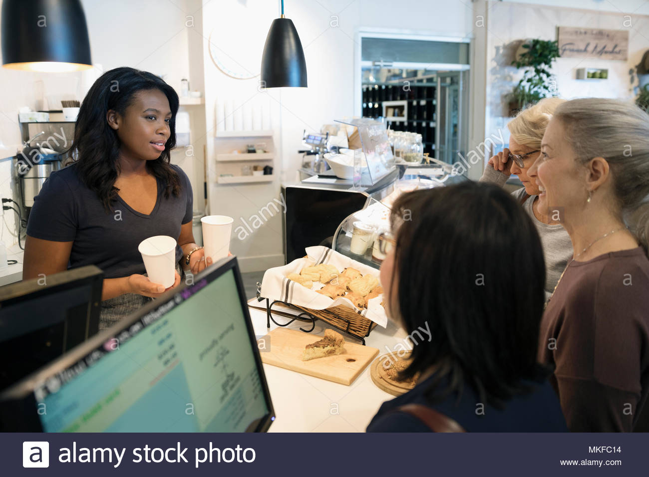 Female worker serving coffee to senior women in bakery - Stock Image