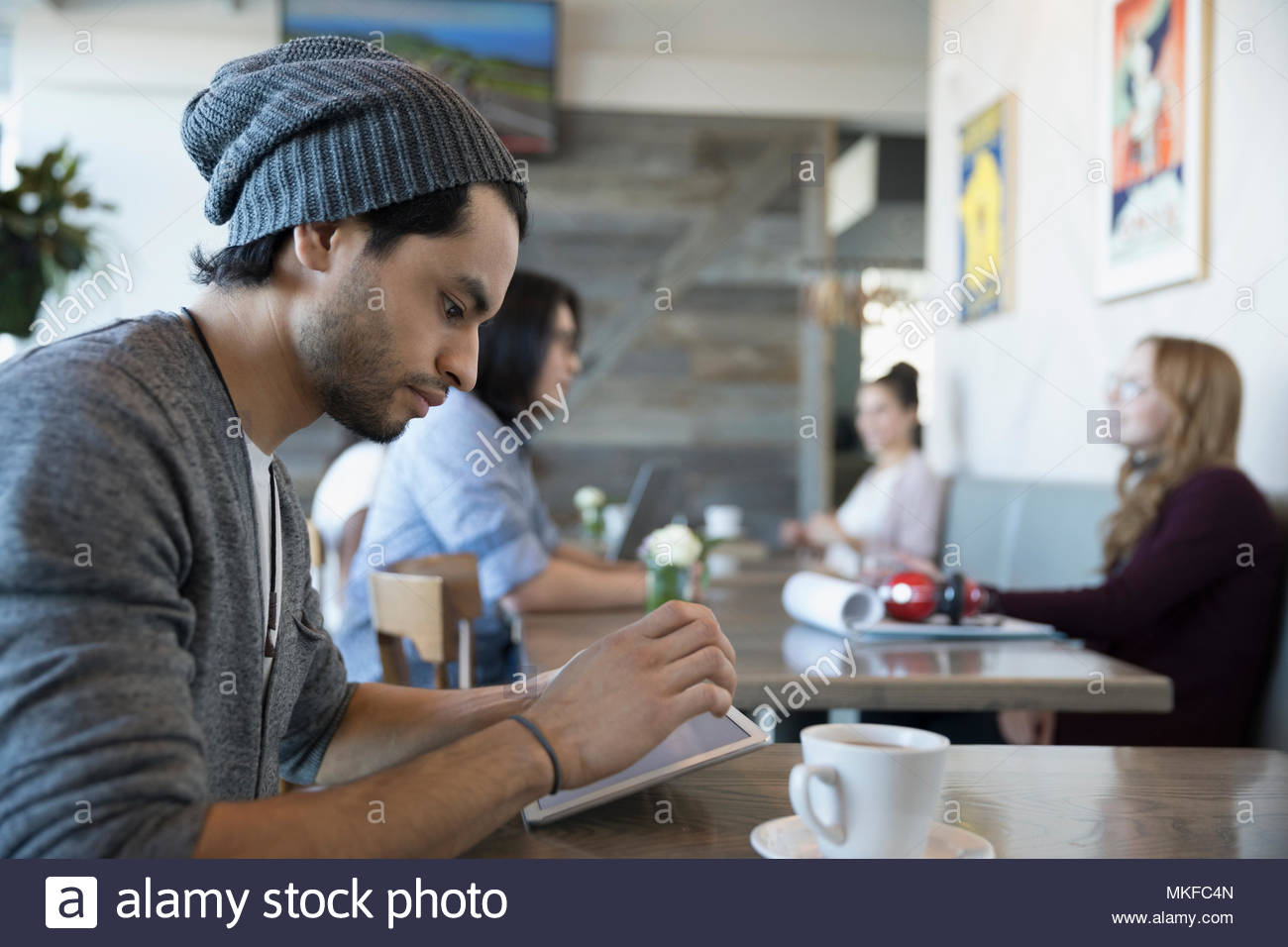Young man using digital tablet and drinking coffee in cafe - Stock Image