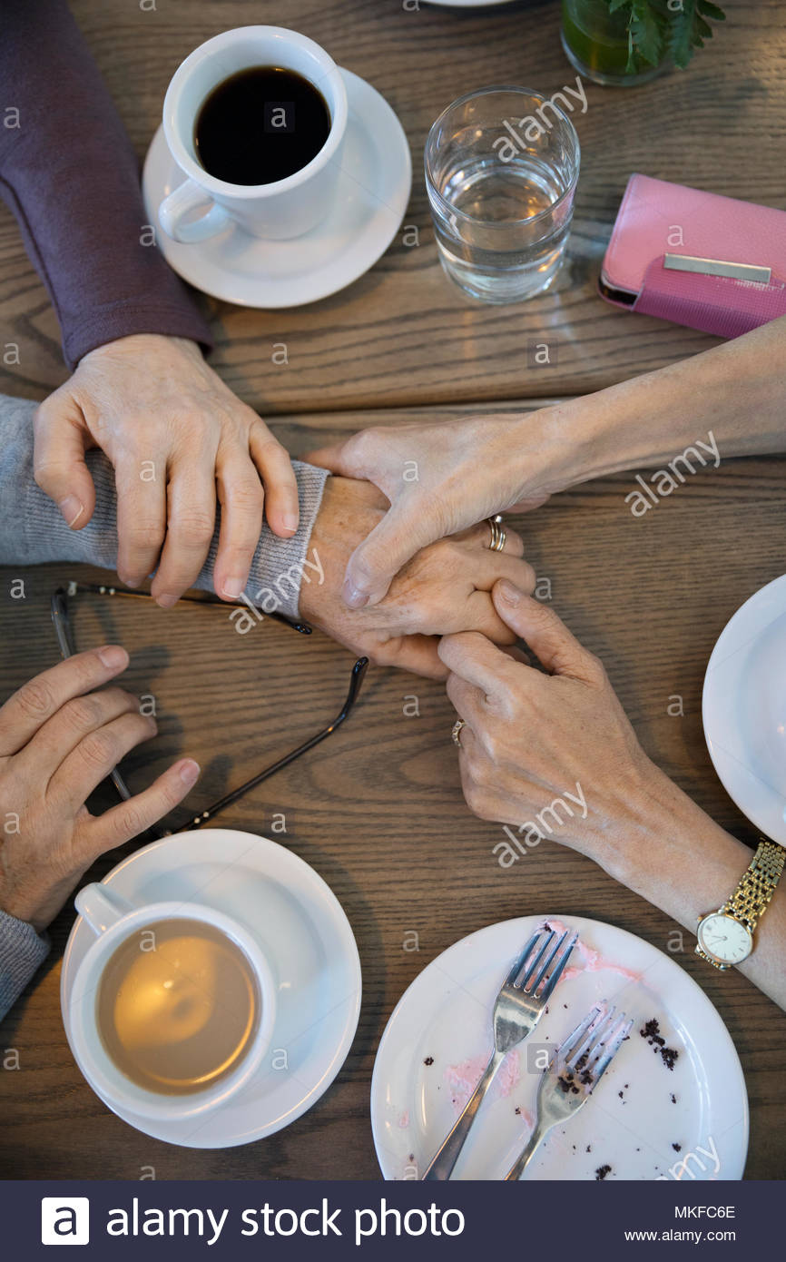 View from above women holding hands, comforting friend in cafe - Stock Image