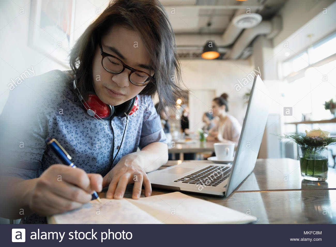 Creative young man writing in notebook, working at laptop in cafe - Stock Image