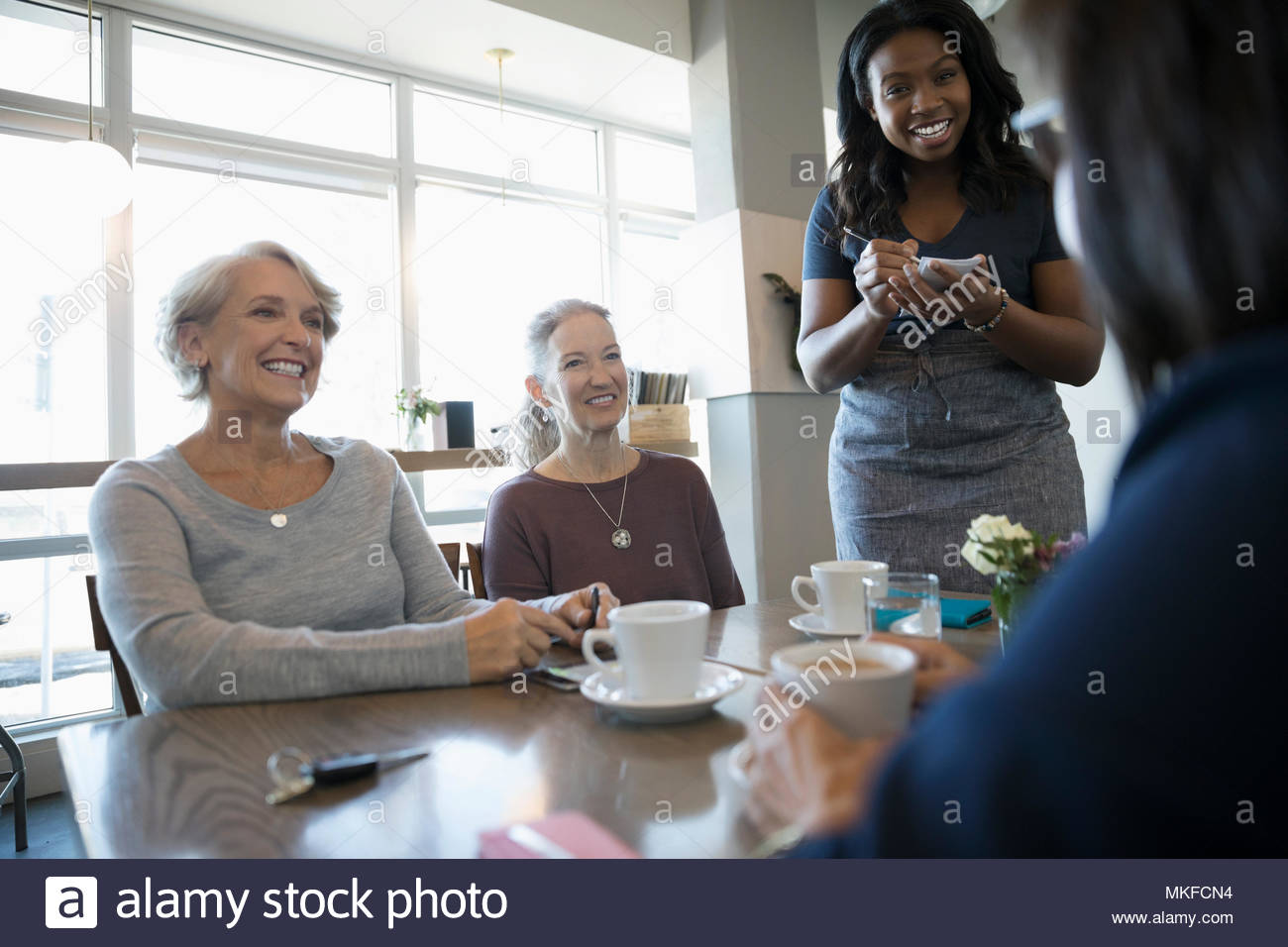 Active senior women friends ordering from waitress in cafe - Stock Image