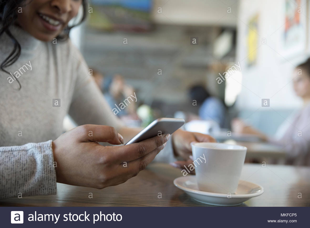 Close up woman using smart phone, drinking coffee in cafe - Stock Image