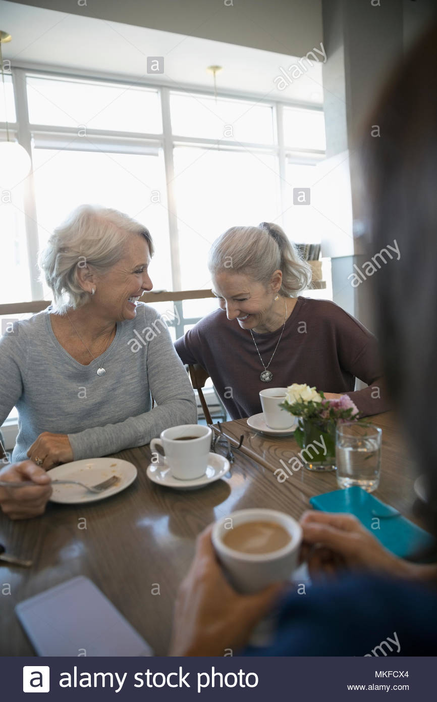 Laughing, active senior women drinking coffee in cafe - Stock Image
