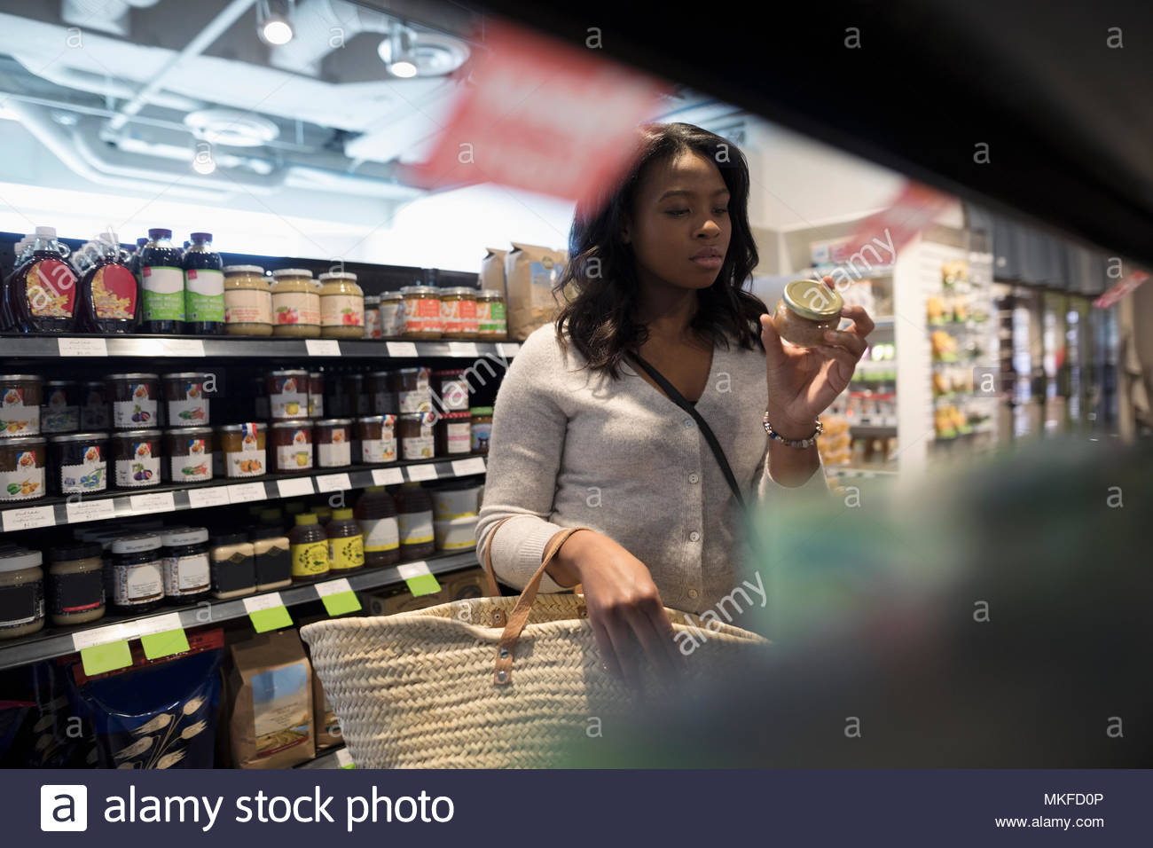 Young woman grocery shopping, reading label on jar in market aisle - Stock Image