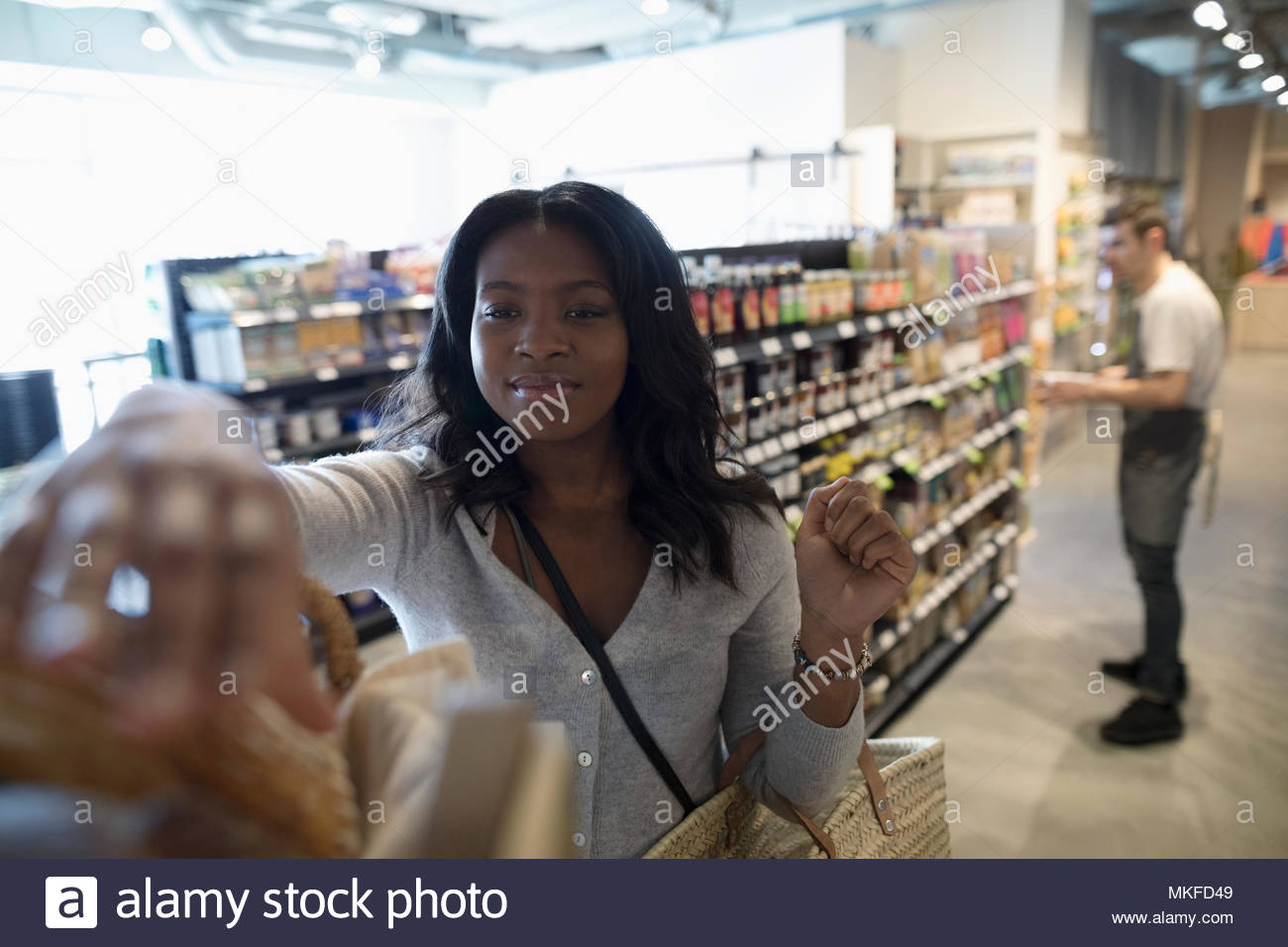 Young woman grocery shopping, reaching for bread in market - Stock Image