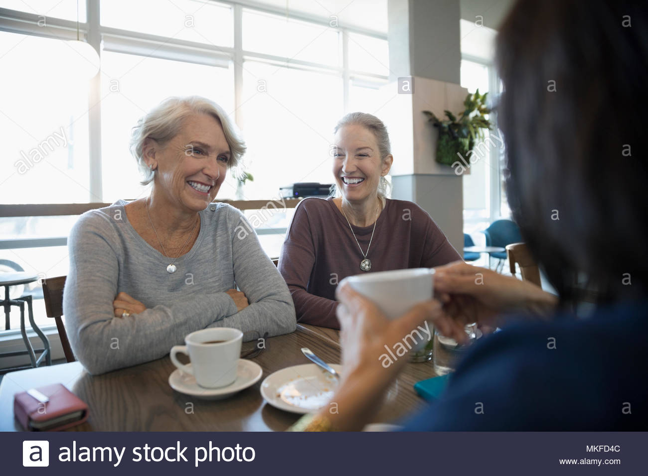 Smiling active senior woman friends talking and drinking coffee in cafe - Stock Image