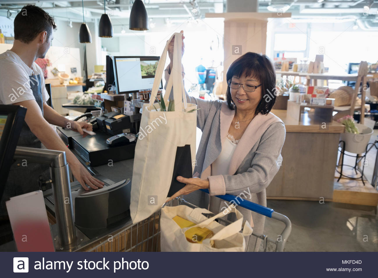 Smiling senior woman placing reusable bags in shopping cart at grocery store checkout - Stock Image