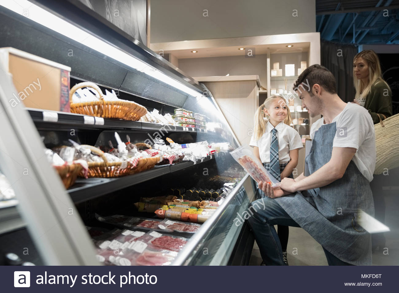 Worker helping mother and daughter grocery shopping in market - Stock Image