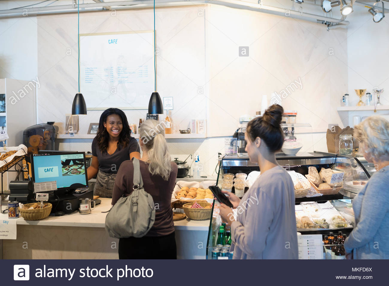 Female worker helping customers in bakery - Stock Image