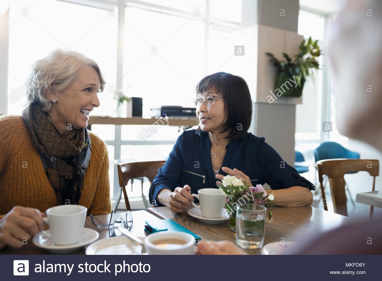 Active senior women friends drinking coffee in cafe - Stock Image