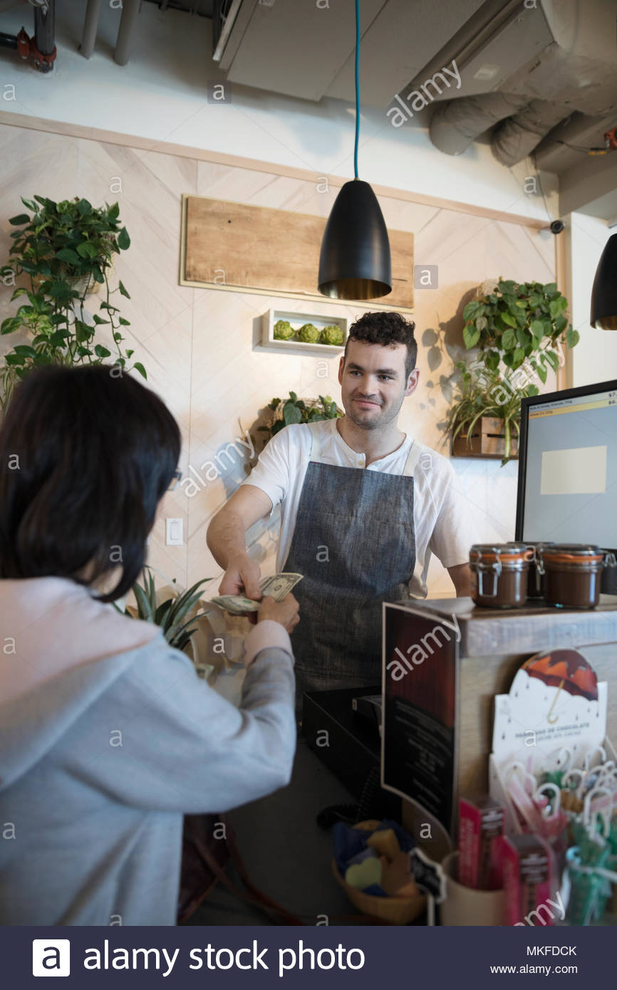 Smiling male worker helping senior woman paying with cash at grocery store checkout - Stock Image