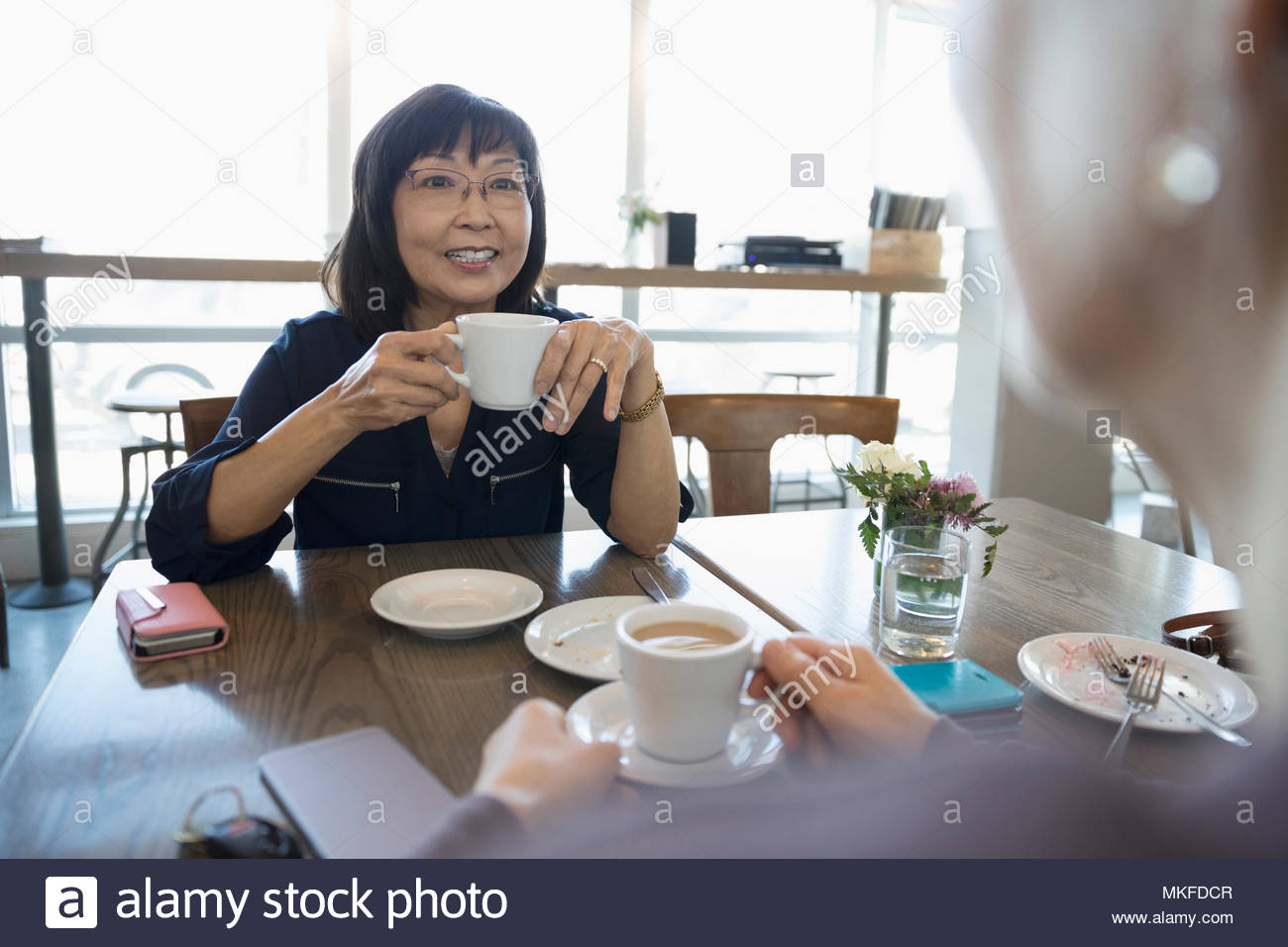 Active senior women friends drinking coffee and talking at cafe - Stock Image