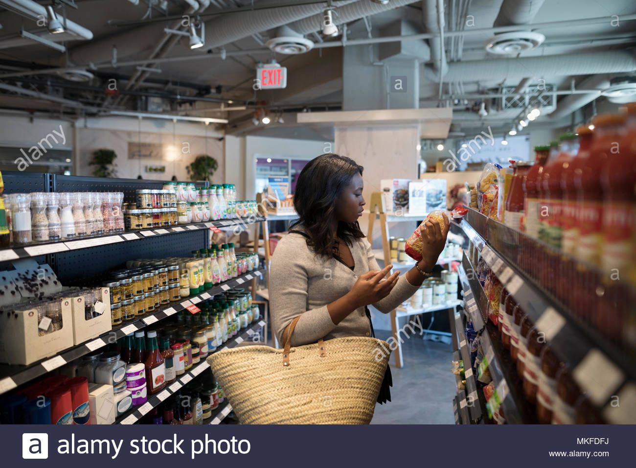 Young woman grocery shopping, reading label on package in market aisle - Stock Image