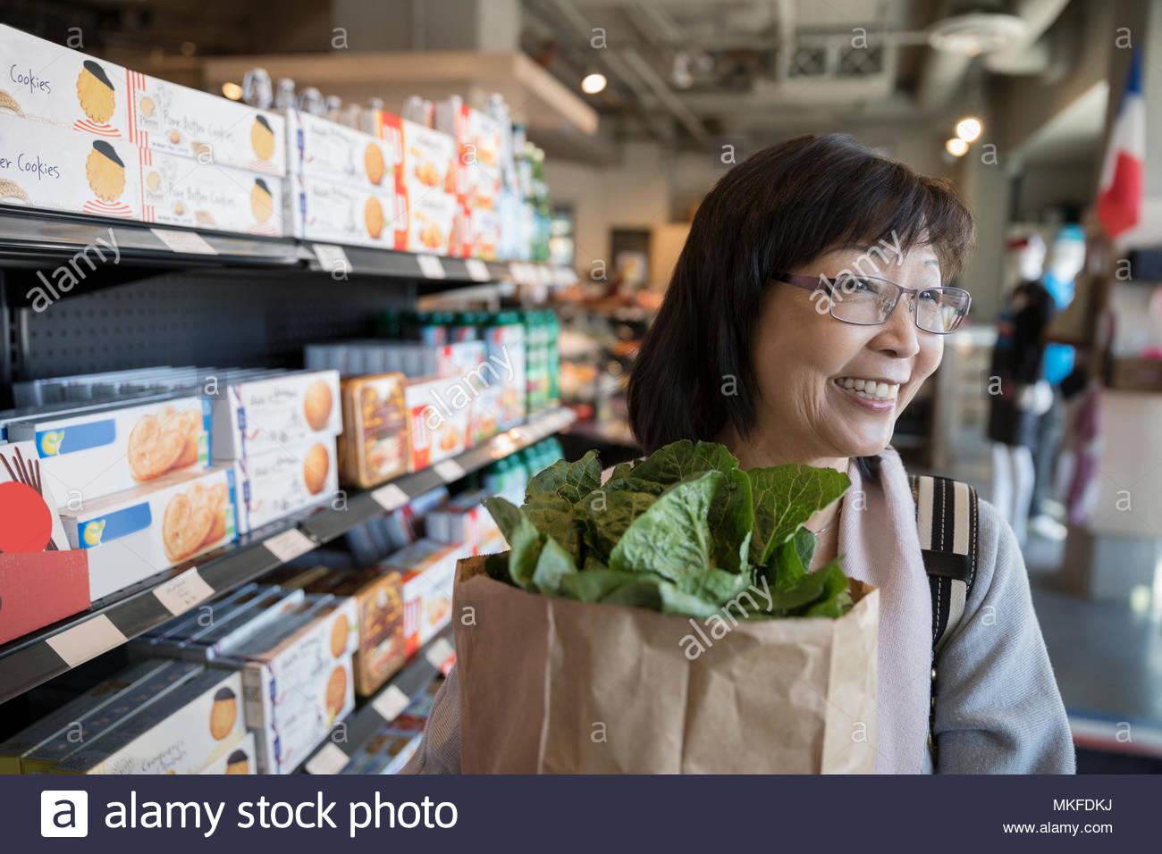 Smiling female senior woman grocery shopping in market aisle - Stock Image