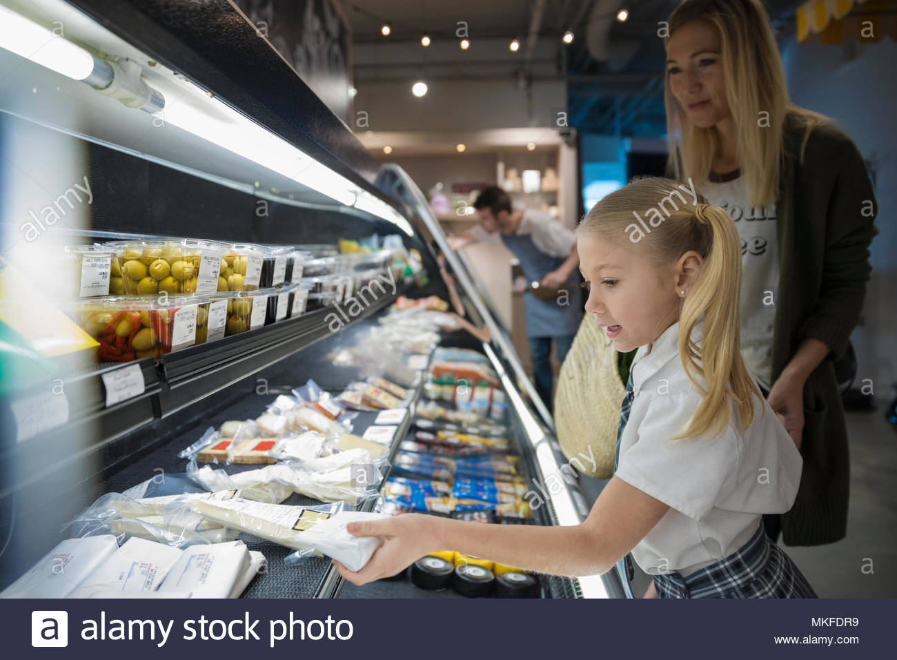 Mother and daughter grocery shopping in market - Stock Image