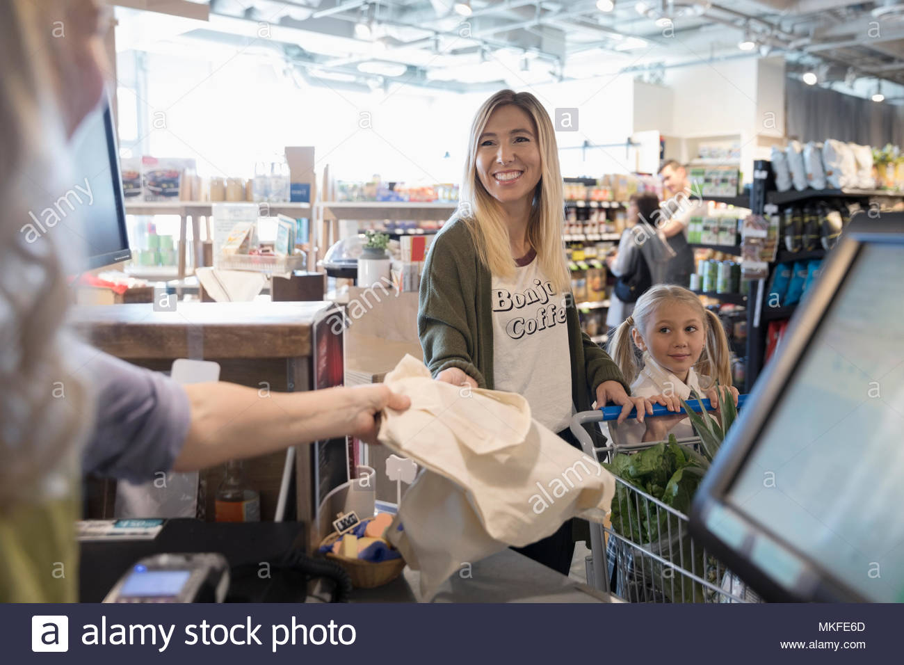 Mother and daughter at grocery store checkout - Stock Image