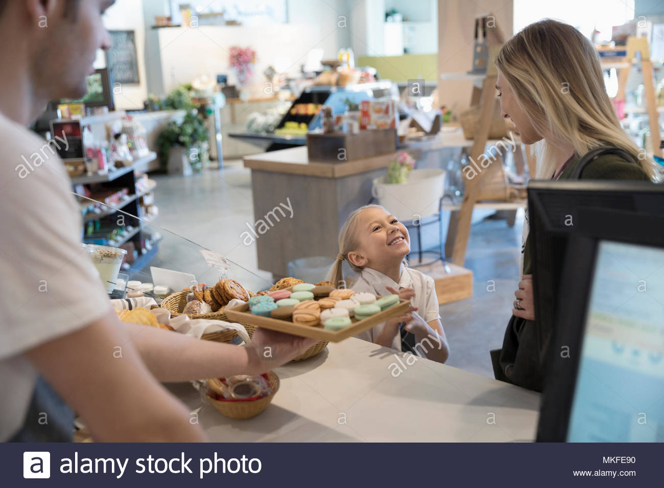 Worker offering eager girl macaron cookie in bakery at market - Stock Image