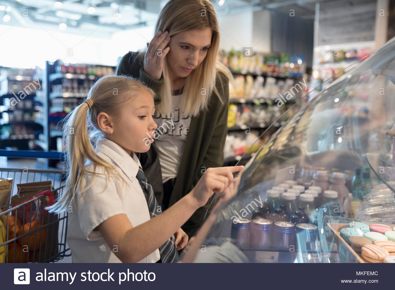 Mother watching daughter pointing at desserts in bakery display case in market - Stock Image