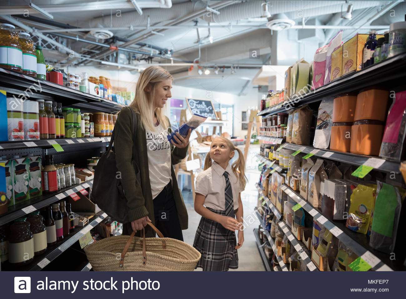 Mother and daughter in school uniform grocery shopping in market aisle - Stock Image