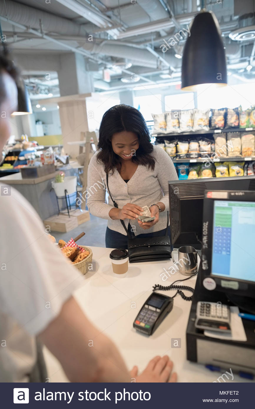 Woman paying for coffee at market checkout counter - Stock Image