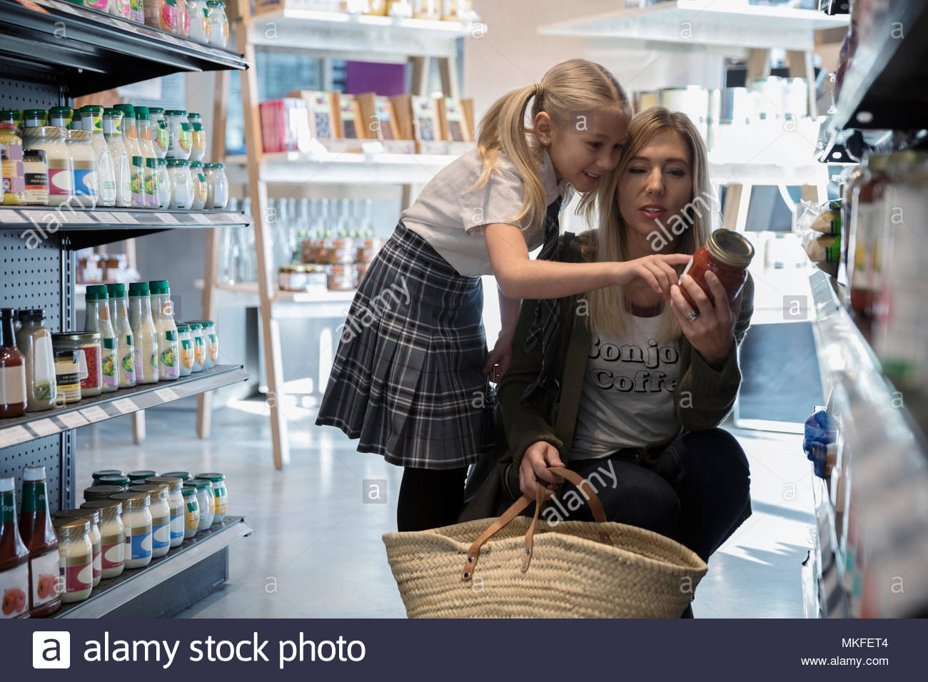 Mother and daughter in school uniform grocery shopping, reading label on can in market aisle - Stock Image