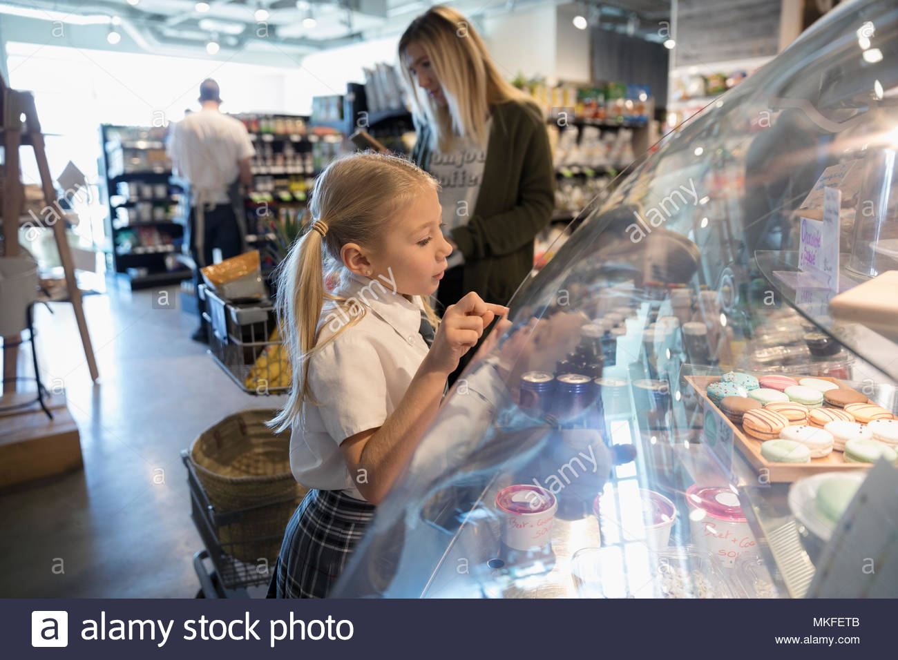 Curious girl browsing desserts in bakery display case in market - Stock Image
