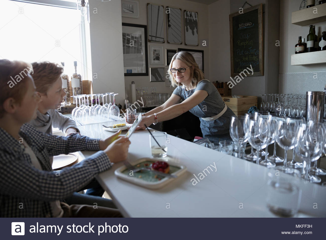 Family business, mother serving food to children at cafe counter - Stock Image