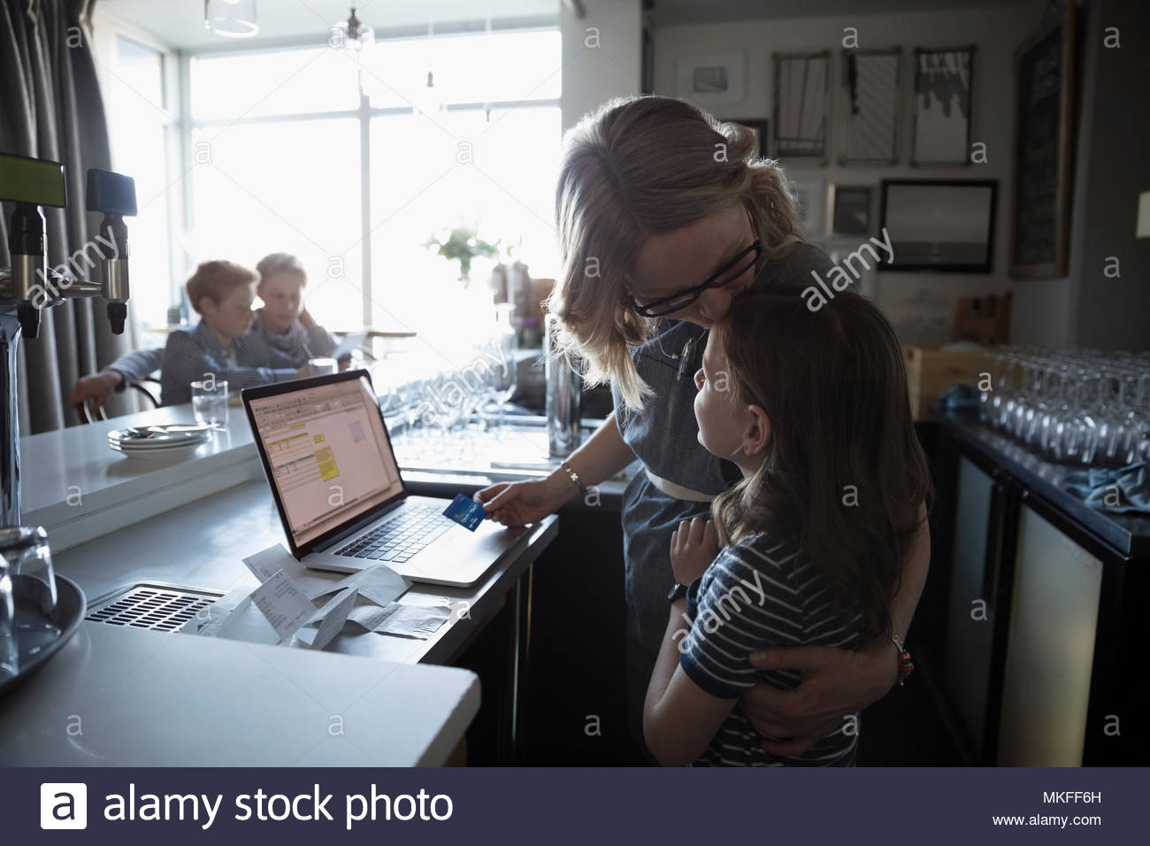 Affectionate family business mother and daughter hugging at laptop in cafe - Stock Image