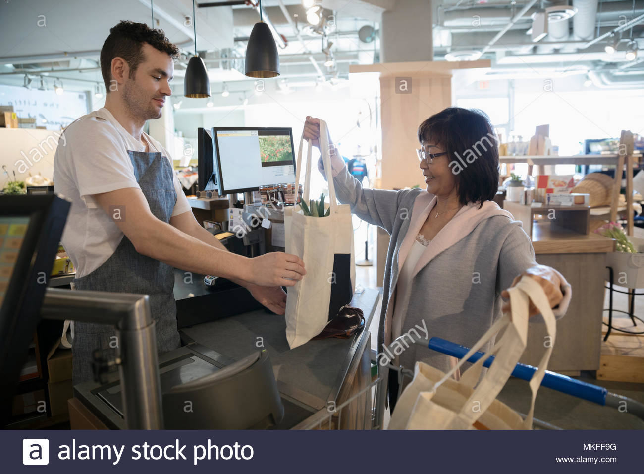 Male worker helping senior woman with reusable bags at grocery store checkout - Stock Image