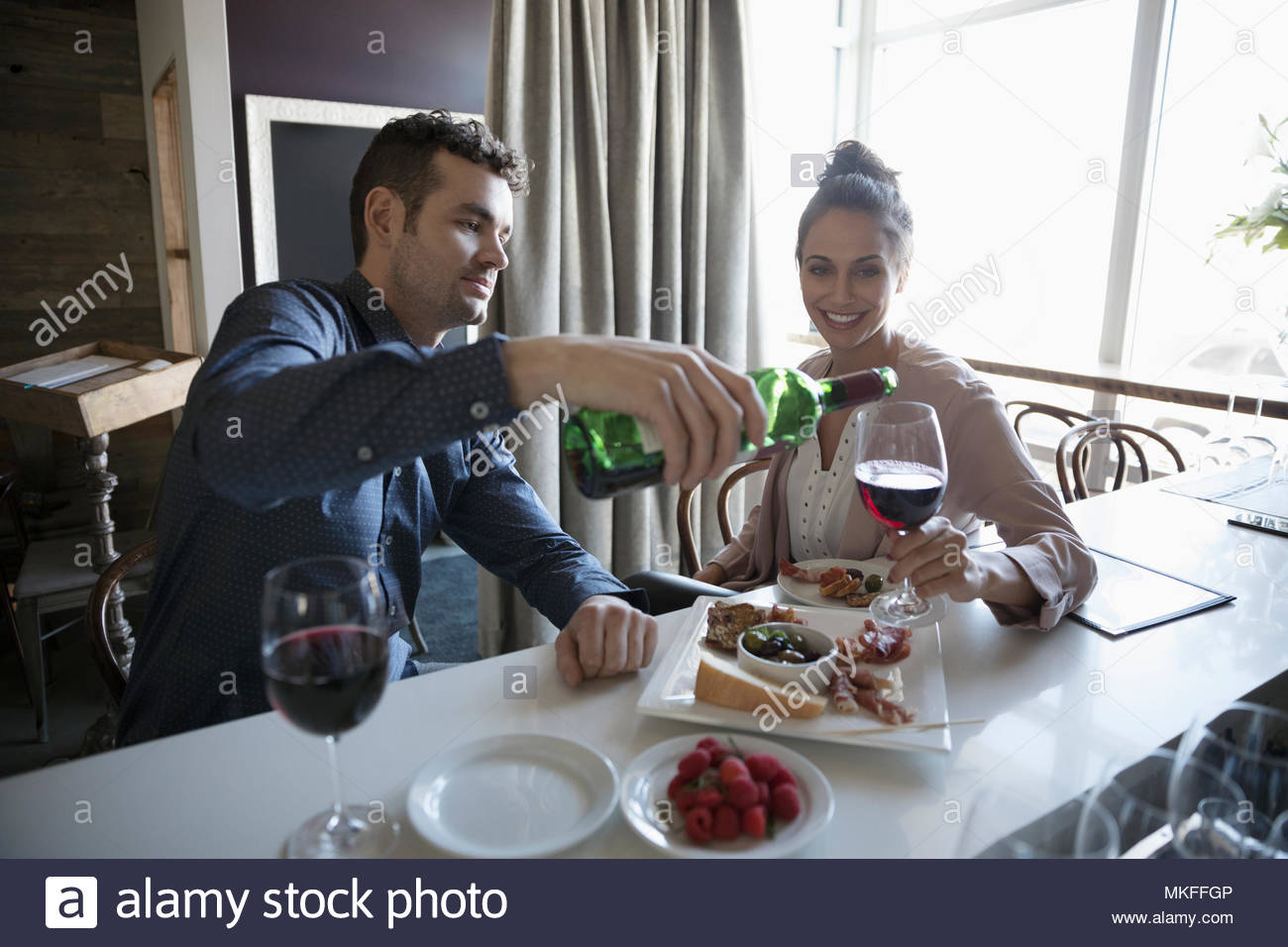 Young couple on date pouring red wine at bar - Stock Image