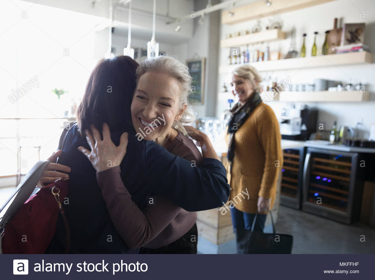 Happy senior women friends greeting, hugging in cafe - Stock Image