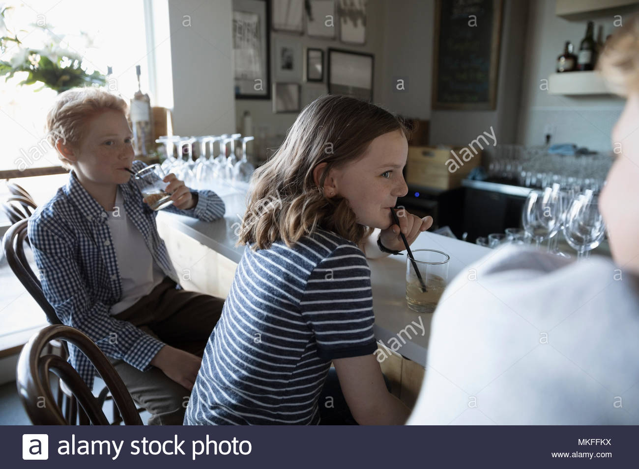 Brother and sister drinking in cafe - Stock Image