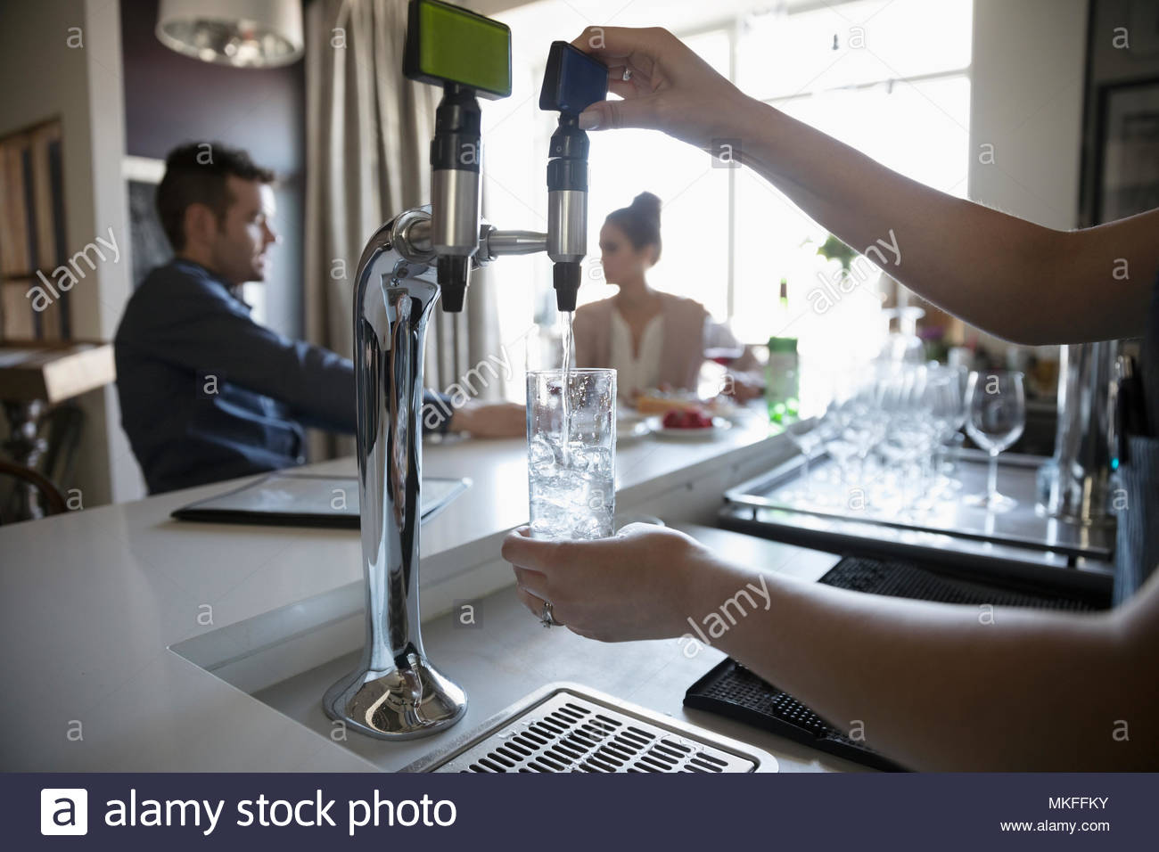 Bartender pouring water in bar - Stock Image