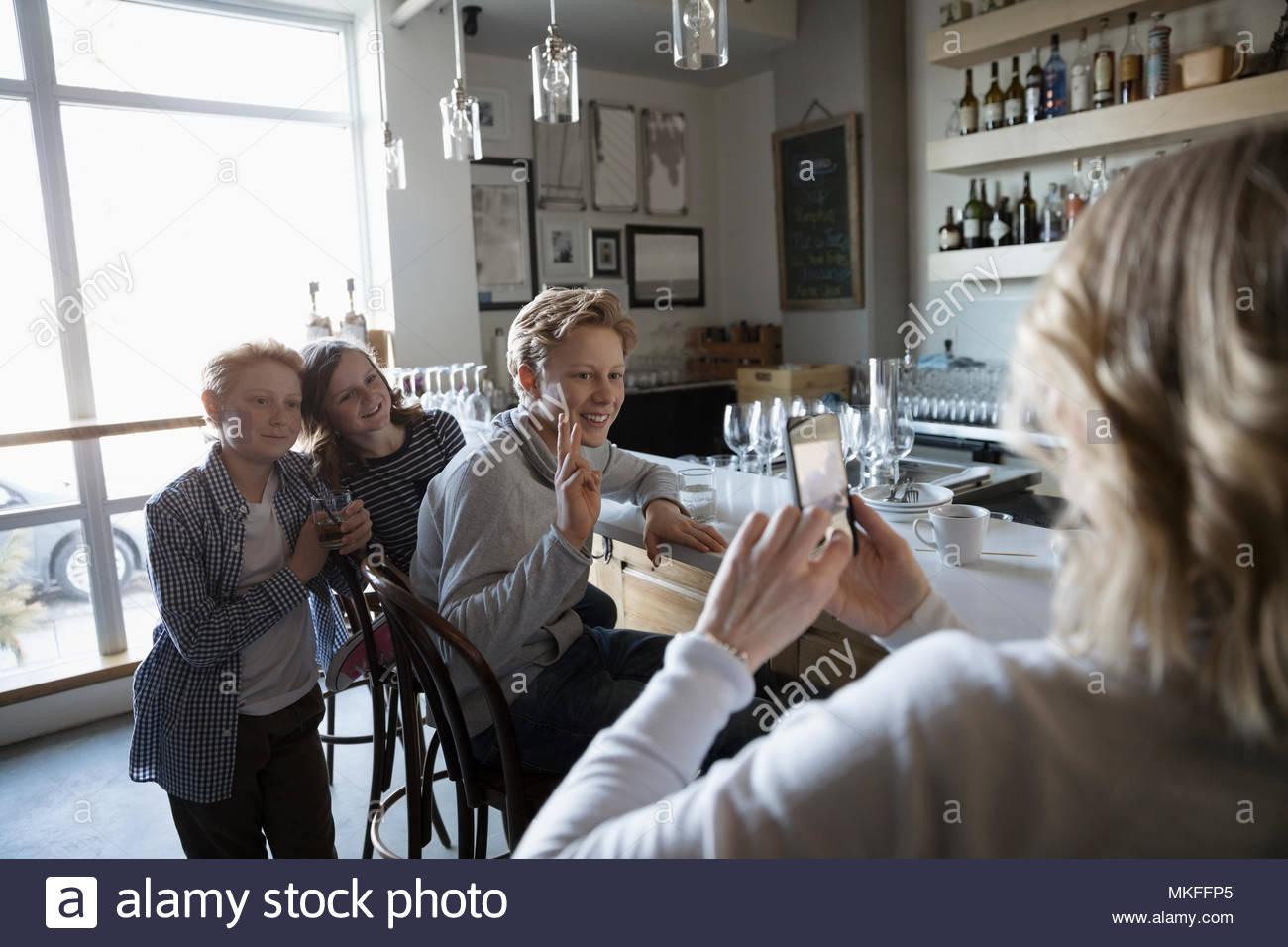 Mother with camera phone photographing children in bar - Stock Image