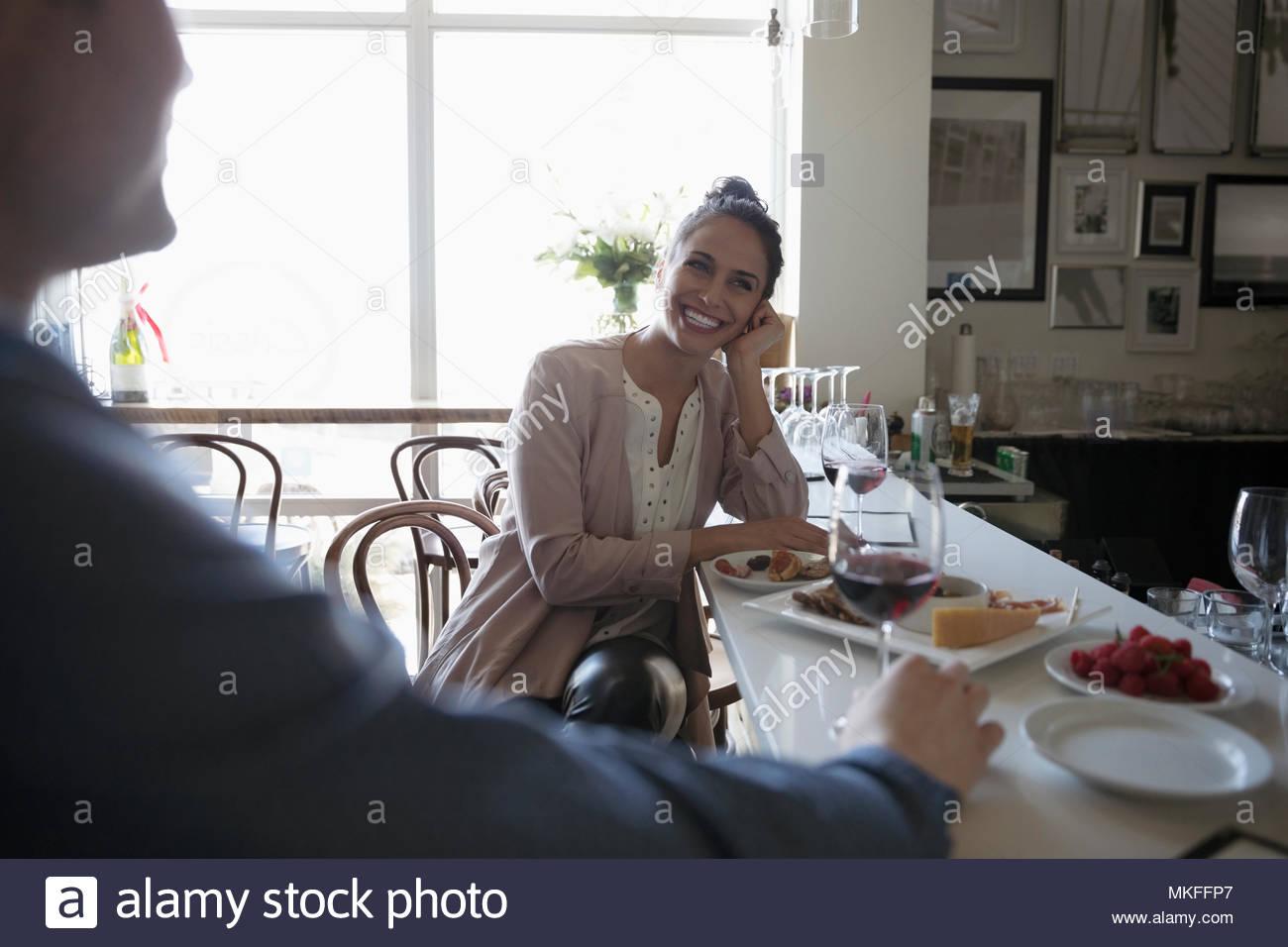 Smiling woman enjoying date at bar - Stock Image