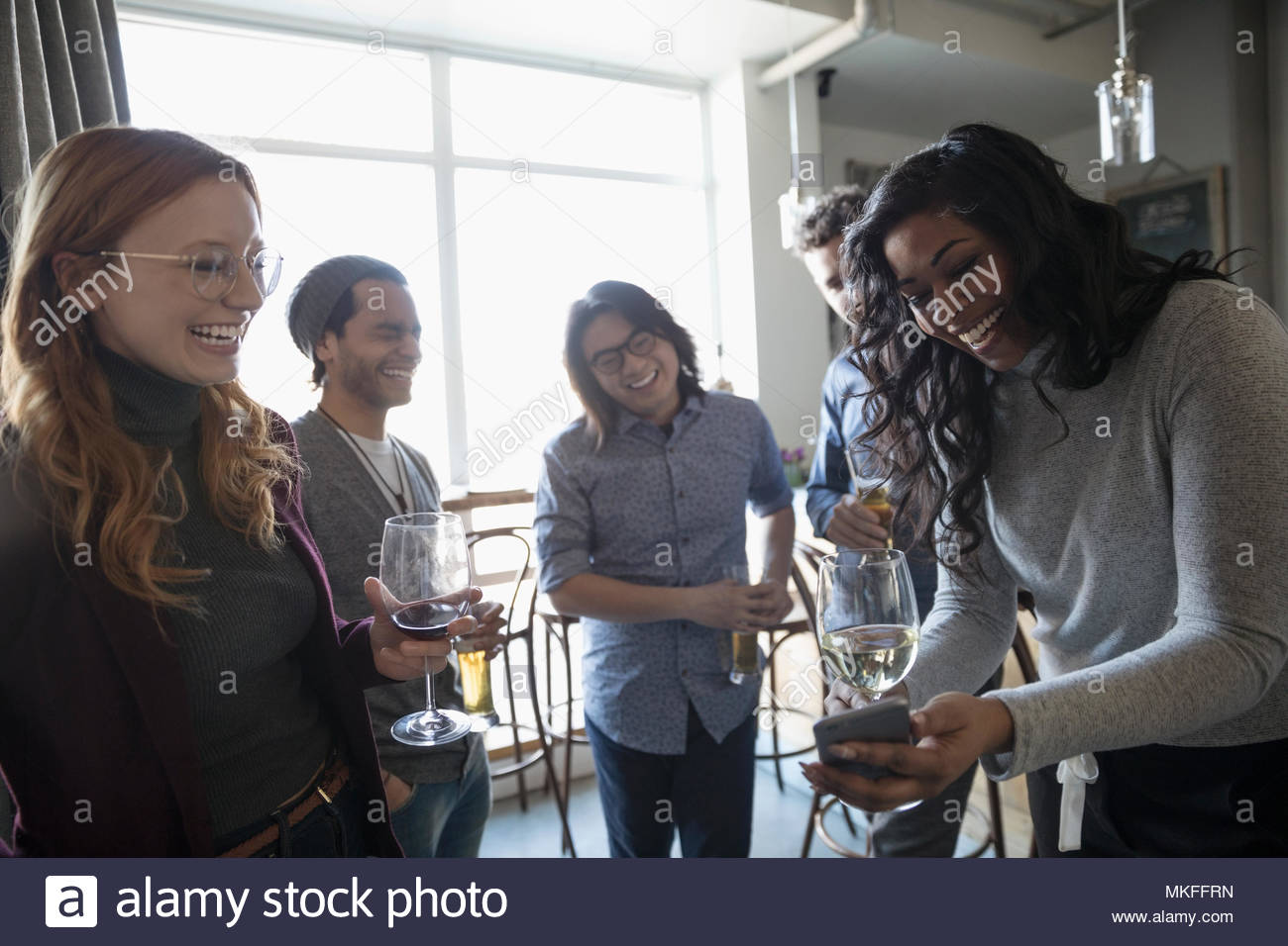 Young friends with smart phone drinking wine, enjoying happy hour in bar Stock Photo