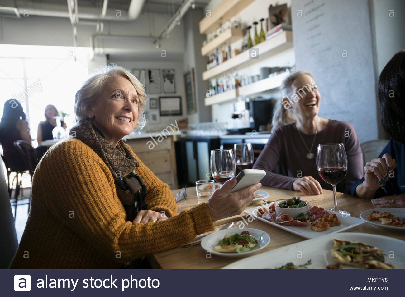 Smiling active senior woman with smart phone eating and drinking red wine with friends in cafe - Stock Image