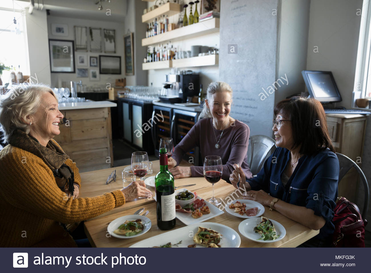 Active senior women friends eating and drinking wine in cafe - Stock Image