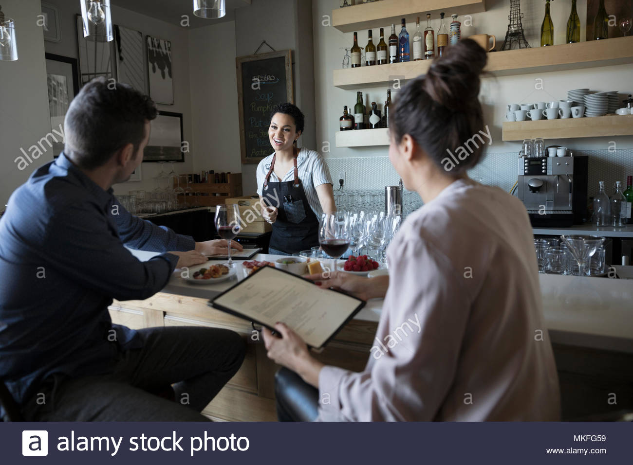 Young couple on date ordering from bartender in bar - Stock Image