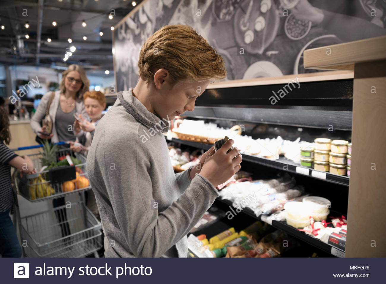 Boy grocery shopping, browsing cheese in market - Stock Image
