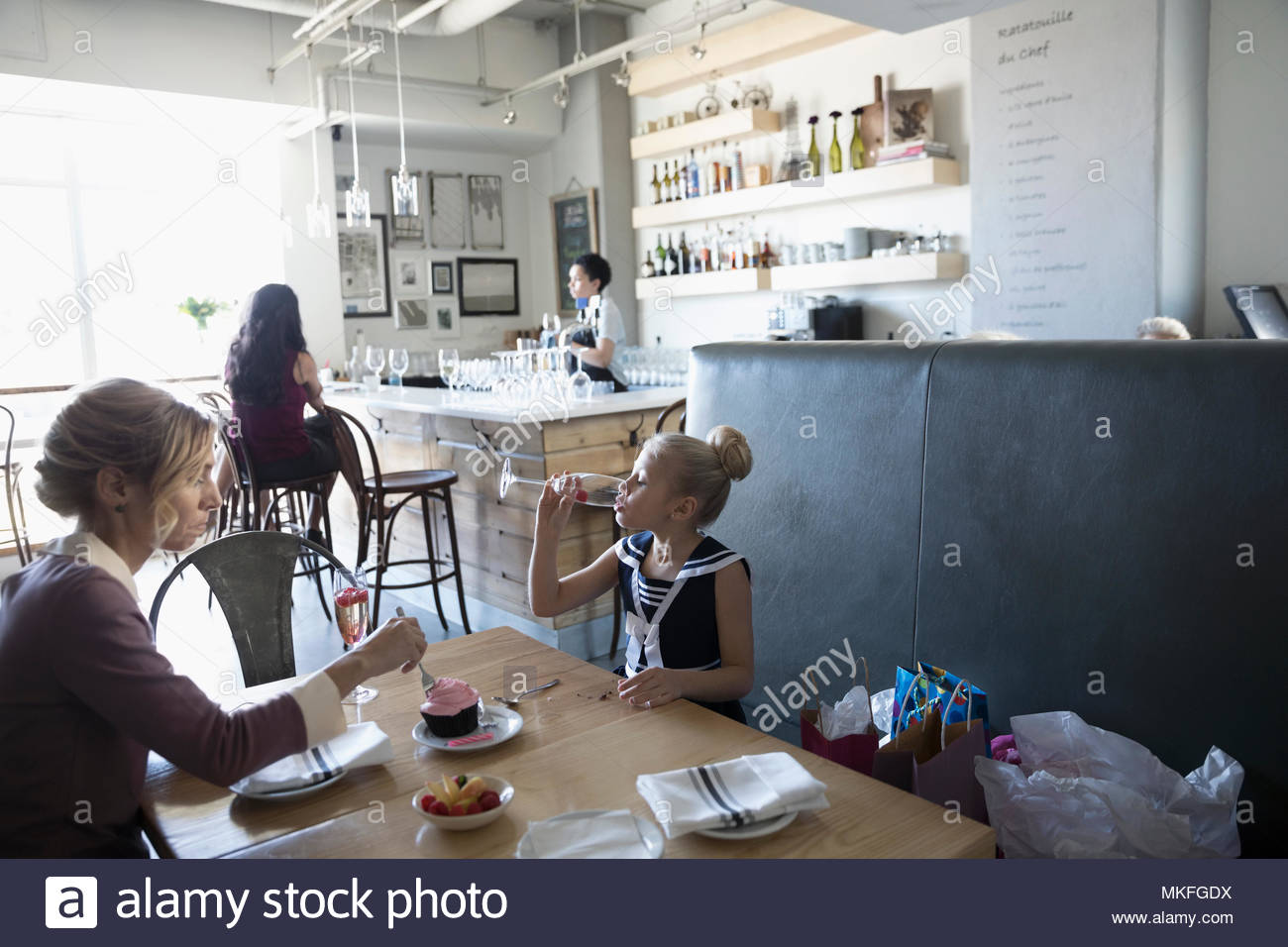 Mother and daughter celebrating birthday, eating cupcake in cafe - Stock Image