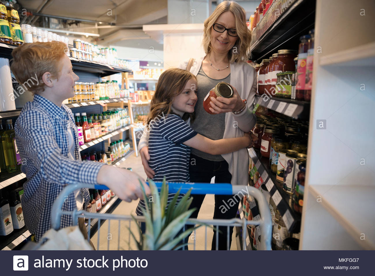 Mother and children grocery shopping in market - Stock Image