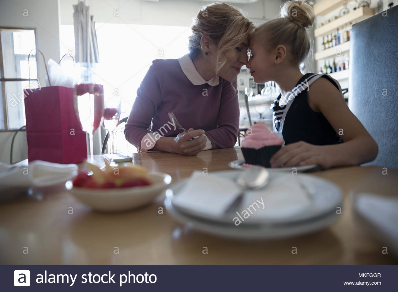 Affectionate mother and daughter celebrating birthday in cafe - Stock Image