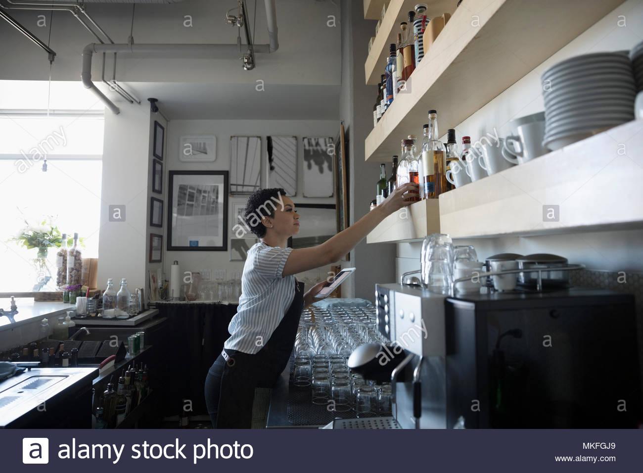 Female bartender organizing alcohol bottles in bar - Stock Image